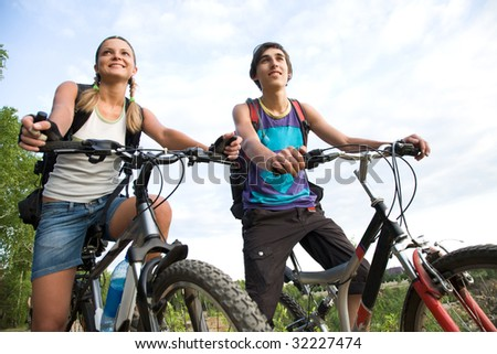 Couple of cyclers on their bikes outdoors in natural envirionment - stock photo