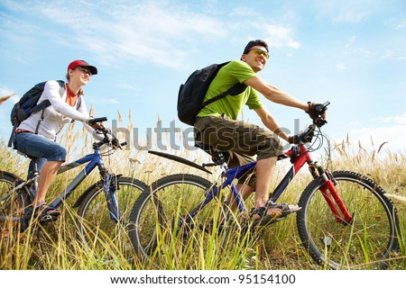 Couple of cyclists riding bicycles in meadow - stock photo