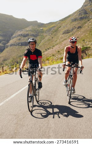 Couple of cyclists riding bicycles on a country road. Fit young people cycling down hill. Triathlon race preparation on open road. - stock photo