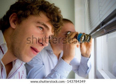 couple of detectives observe through a window by means of the field-glass - stock photo