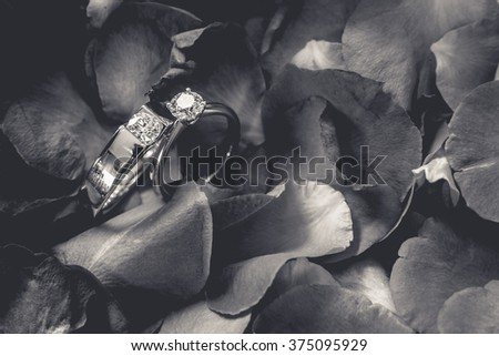 Couple of diamond rings on rather withered petal rose flowers. - (Mood and tone) - stock photo