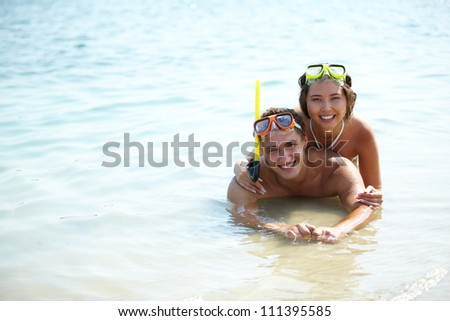 Couple of divers in scuba masks enjoying themselves in water