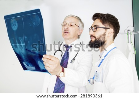 couple of doctors examining an x-ray of a woman's body - stock photo