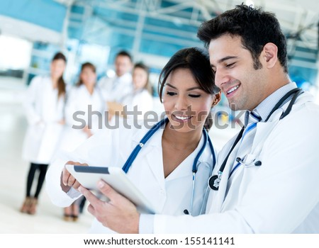 Couple of doctors talking and using a tablet computer