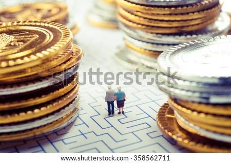 Couple of elderly walk through the maze, money problems - stock photo