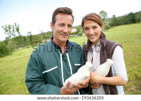 Couple of farmers holding bottles of milk - stock photo