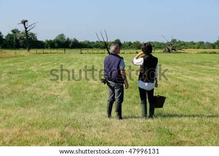 Couple of farmers walking outside in cattle field