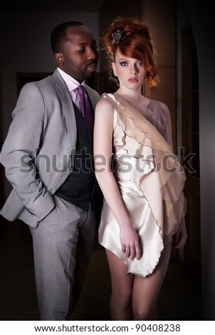 Couple of fashion dressed people - black american man and red haired young woman. Formal party