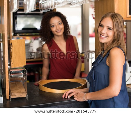 Couple of female baristas standing inside their coffee house