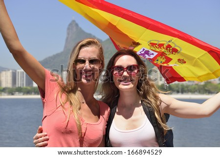 Couple of female sport fans holding the Spanish flag in Rio de Janeiro with Christ the Redeemer in the background. - stock photo