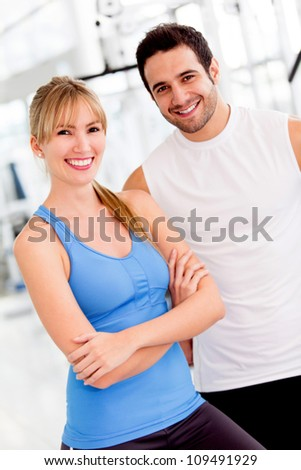 Couple of fit people at the gym looking happy - stock photo