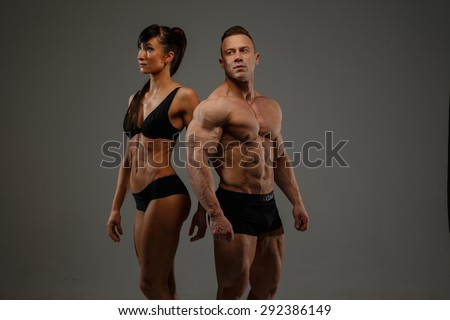 Couple of fitness woman and man bodybuilder in underwear. Isolated on grey background. - stock photo