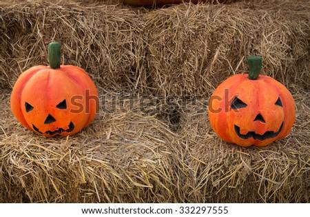 Couple of foam Halloween pumpkins on haystack in Halloween theme restaurant - stock photo