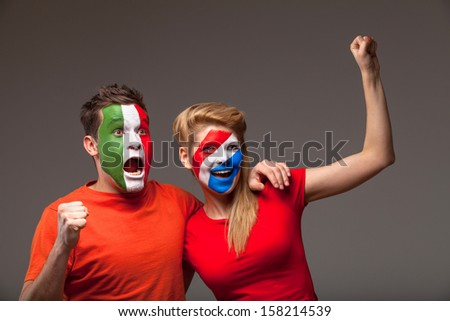 Couple of footbal fans. With face art in red T-shirts - stock photo