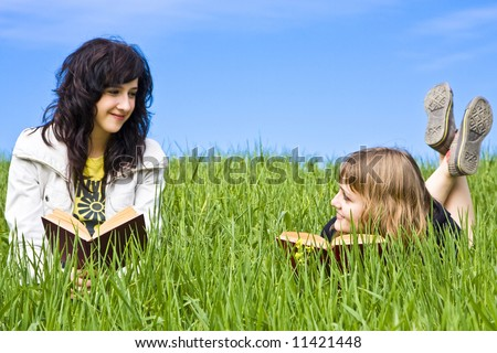Couple of friends enjoying a book in a meadow - stock photo