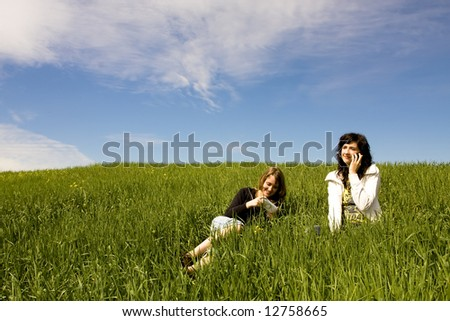 Couple of friends enjoying at meadow - stock photo