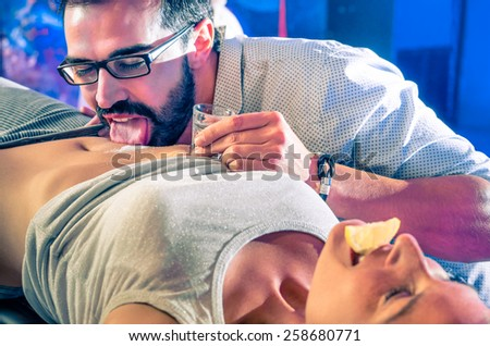 Couple of friends having fun in disco night club with body tequila party - Nightlife with crazy drunk game for young people - Vintage look with soft focus on glass and salt with shallow depth of field - stock photo