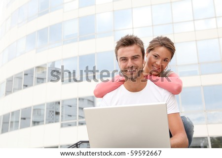 Couple of friends in college campus with laptop computer - stock photo