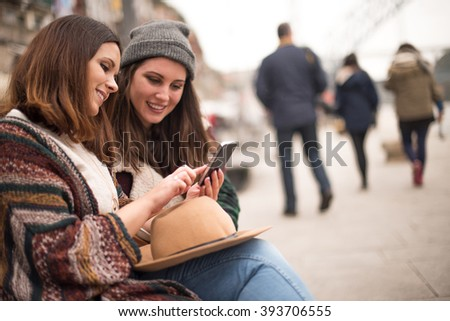 Couple of friends with a smartphone in the city street
