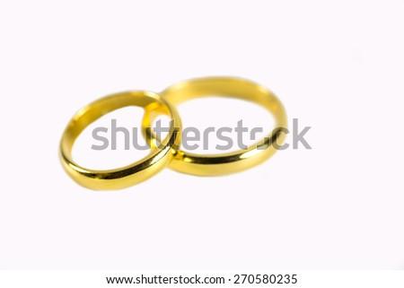 couple of gold wedding rings on white background - stock photo
