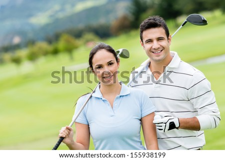 Couple of golf players at the course looking happy  - stock photo