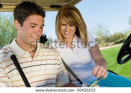 Couple of golfers riding in golf cart