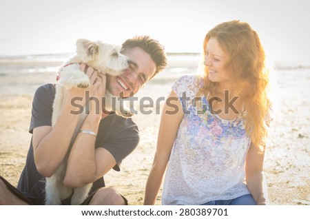 Couple of guys playing with their dog on the beach - stock photo