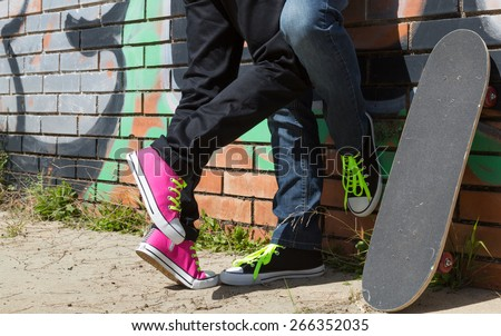 Couple of guys with his skateboard next to a wall with graffiti - stock photo