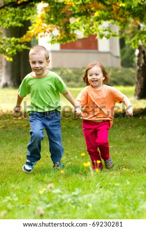 Couple of happy kids running on the grass. - stock photo