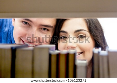 Couple of happy students hiding behind books at the library - stock photo