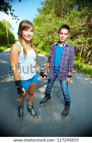 Couple of happy teens looking at camera outside - stock photo