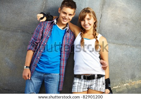 Couple of happy teens looking at camera outside