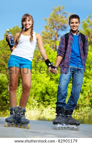 Couple of happy teens on roller skates looking at camera outside - stock photo