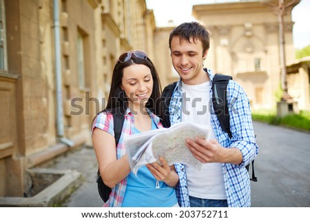 Couple of happy travelers studying map of ancient town - stock photo