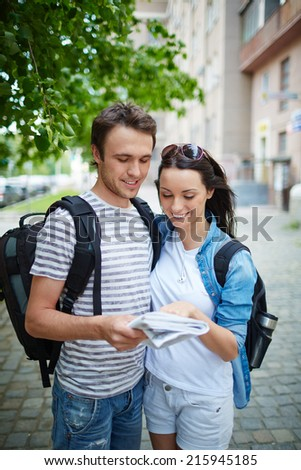 Couple of happy travelers studying their route in guide - stock photo