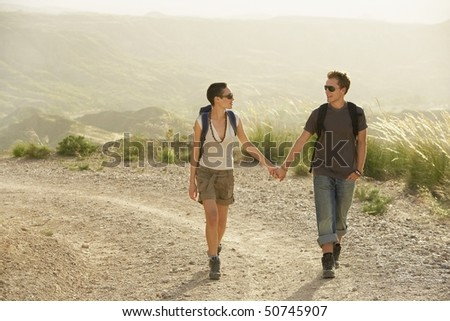 Couple of hikers holding hands, walking on country road - stock photo