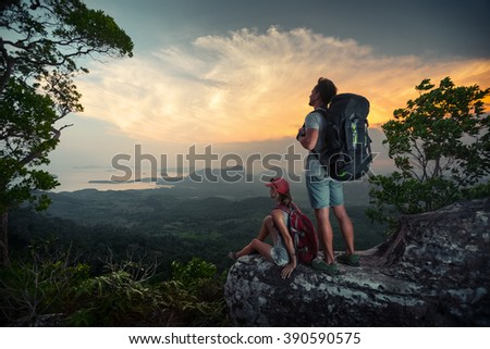 Couple of hikers relaxing on the mountain and watching sunset over the valley