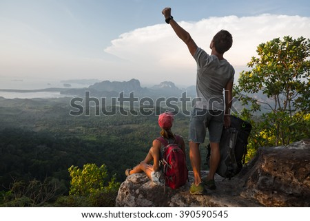Couple of hikers relaxing on top of the mountain - stock photo