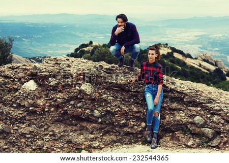 Couple of hikers resting sitting on mountain hill with beautiful view on background, stylish teenager guys sitting on the rock, cute and stylish romantic couple at holidays leisure like county style