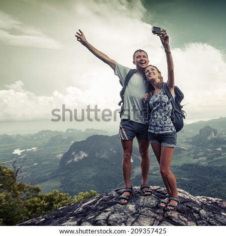 Couple of hikers taking photo of themselves on top of the mountain with green valley on the background - stock photo