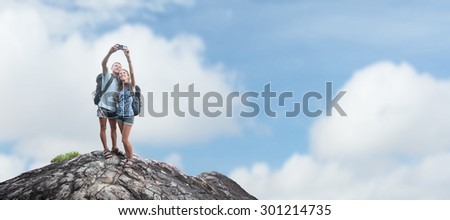 Couple of hikers with backpacks taking selfie on top of the mountain - stock photo
