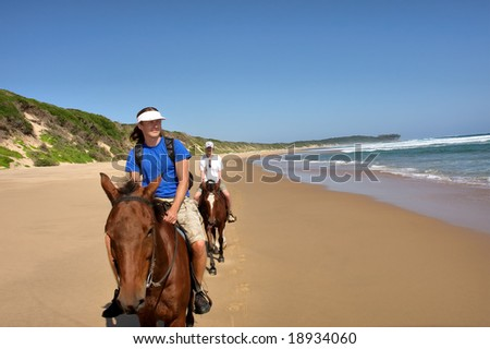 Couple of horse riders on beach. Shot in Sodwana Bay Nature Reserve, KwaZulu-Natal province, Southern Mozambique area, South Africa. - stock photo