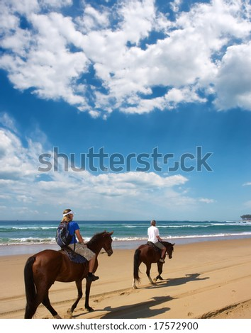 Couple of horse riders on beach under dramatic skies.