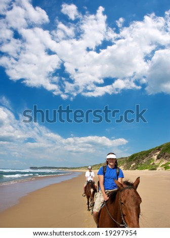 Couple of horse riders on beach under dramatic skies. Shot in Sodwana Bay Nature Reserve, KwaZulu-Natal province, Southern Mozambique area, South Africa. - stock photo