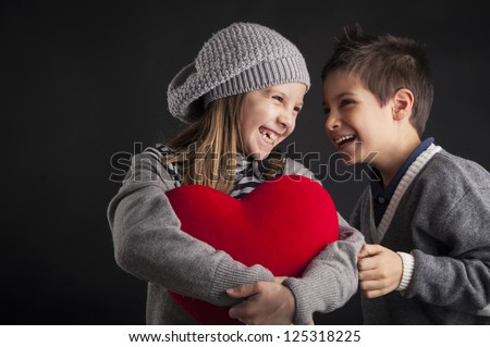 Couple of kids having fun with red heart over black background. Valentines concept. - stock photo