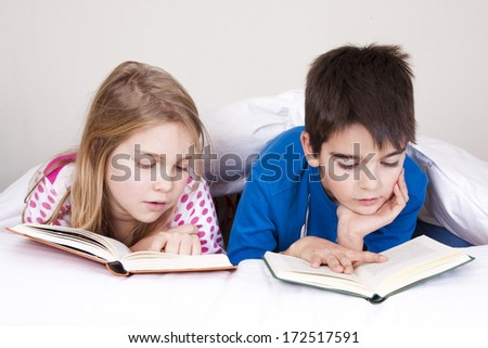 couple of kids in bed covered with blanket reading - stock photo