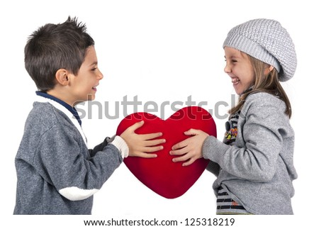 Couple of kids playing with red heart over white background. Valentines concept. - stock photo