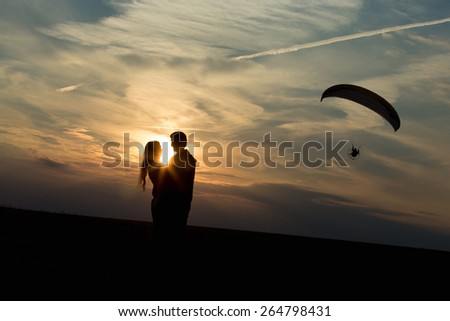 Couple of lovers against vast skyline on the sunset or sunrise, hugging each other, standing on the distance of a kiss, unusual date location, paraglider flying on the background - stock photo