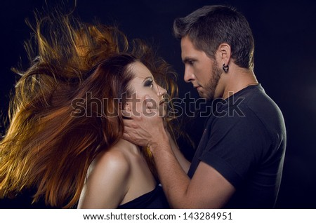 Couple of lovers. Cost profile. The guy holding the girl's face, they look into each other's eyes and her hair develop, on a black background - stock photo