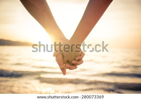 Couple of lovers holding their hands at a beautiful sunset over the ocean - Newlywed couple on a romantic vacation - stock photo